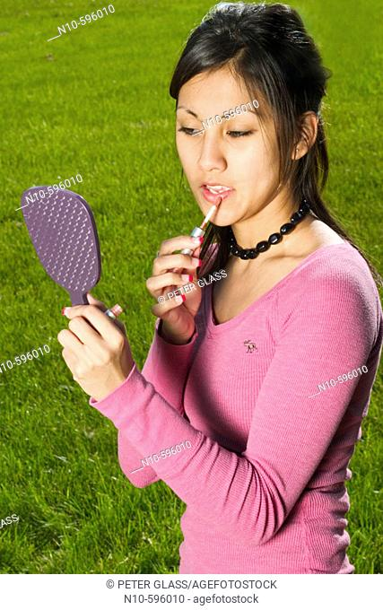 Young Spanish/Asian woman putting on makeup at a park