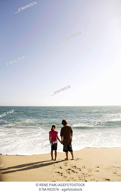 Boy and girl looking out contemplatively at the vast ocean as the sun begins to set