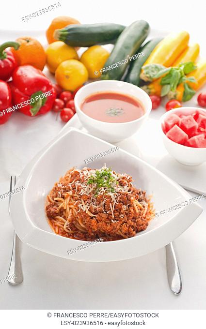 Italian classic spaghetti with bolognese sauce and fresh vegetables on background
