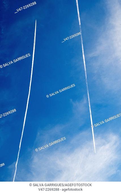 Contrails propel a plane against the blue sky