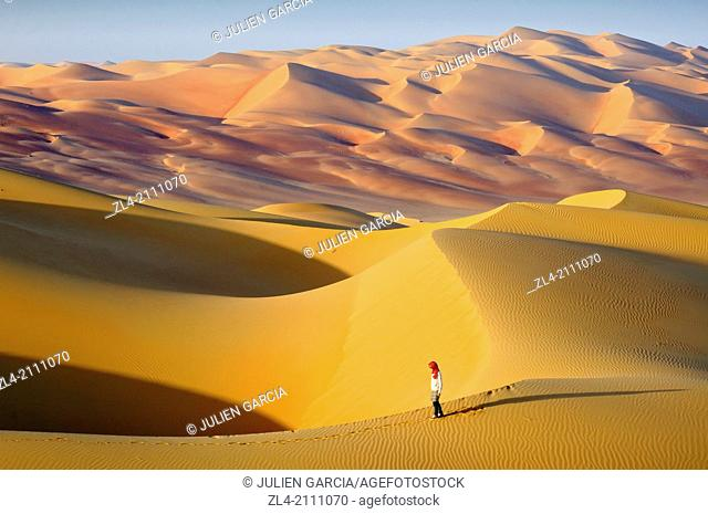 Woman in the sand dunes of the empty quarter desert. United Arab Emirates, UAE, Abu Dhabi, Liwa Oasis, Moreeb Hill, Tal Mireb. Model Released