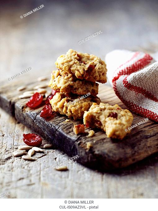 Oat and cranberry cookies, rustic wooden board, vintage tea towel, wooden table