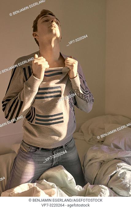 Young sensual man alone on bed at home, emotional, desire, in Munich, Germany