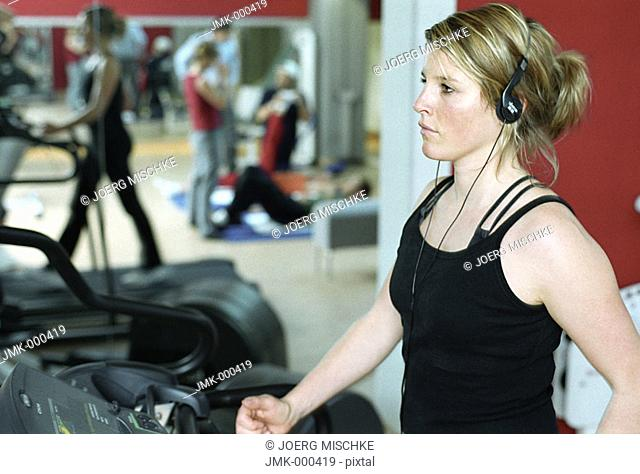 Young woman at the gym, fitness center, walking on the treadmill