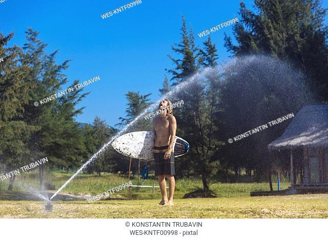 Young man with surfboard refreshing at sprinkler