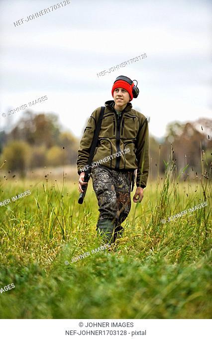 Teenage boy with rifle at hunting