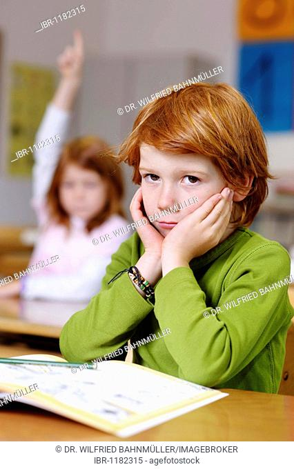 Children in a classroom in primary school, boy daydreaming or looking unsure, thoughtful, sad or frustrated, boys becoming the losers or failures in the...
