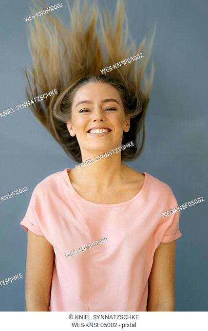 Portrait of smiling young woman tossing her hair