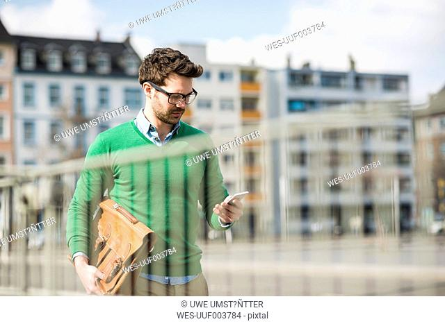 Man in green sweater carrying briefcase, reading text message