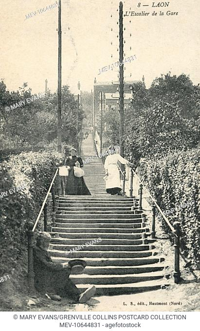 Stairway up to the Railway Station at Laon, Aisne department in Picardy, France. A beggar sits at the foot of the long stair