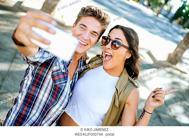 Young couple taking selfie with smartphone