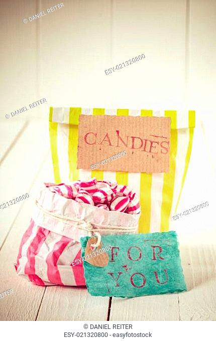 Two colorful striped bags of candies with tags
