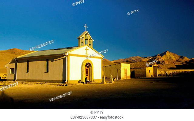 Small white church and woman sitting in front of it in Cordillera de Lipez in southern bolivian Altiplano. The church looks like from western movie