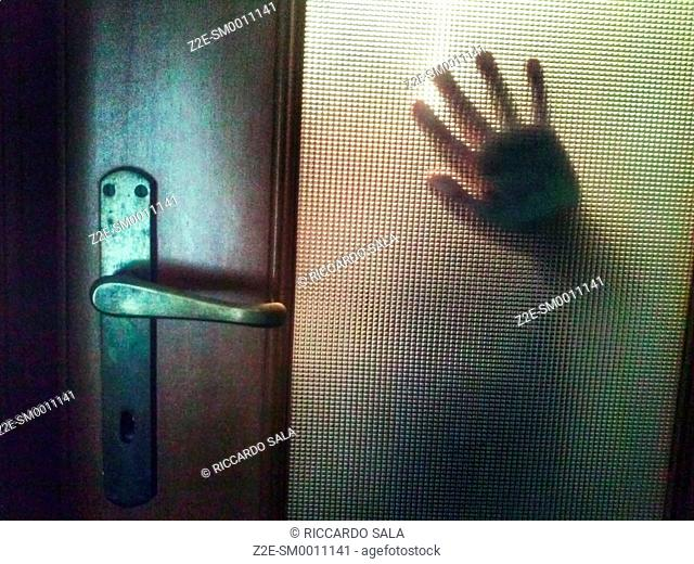 Hand Behind Door Glass