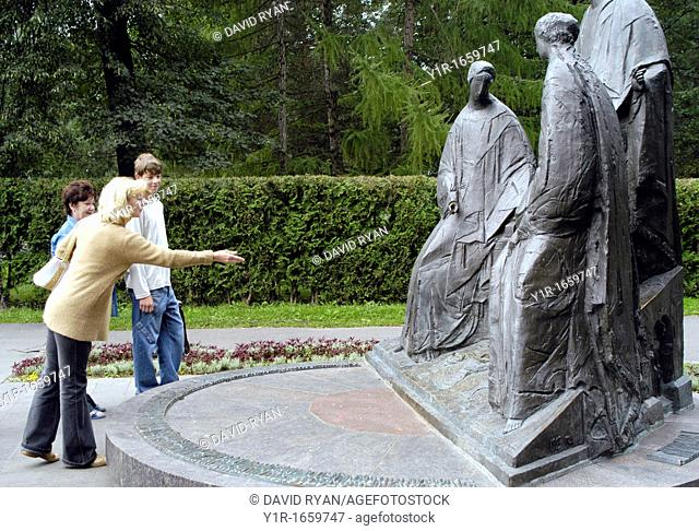 Russia, Yaroslavl, Yaroslavskaya Oblast,Park of Peace, Tossing coins onto a WW2 memorial sculpture for good luck