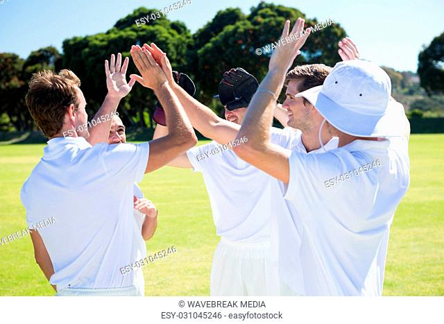 Smiling cricket players celebrating win at field