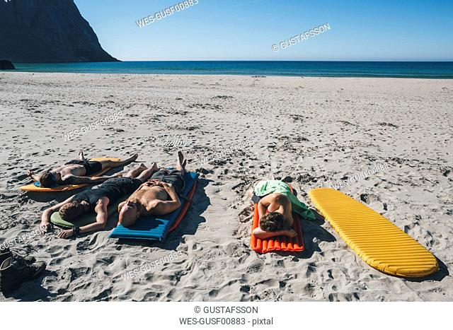 Norway, Lofoten, Moskenesoy, Friends sunbathing on Kvalvika Beach