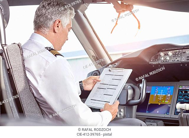 Male pilot with clipboard preparing in airplane cockpit