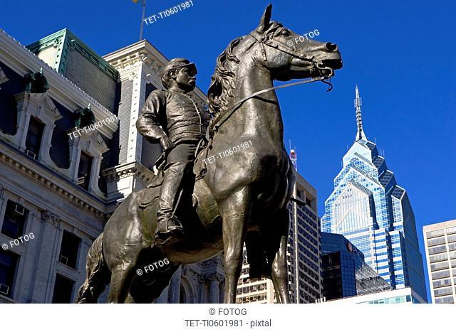USA, Pennsylvania, Philadelphia, Statue depicting man on horse, skyscrapers in background