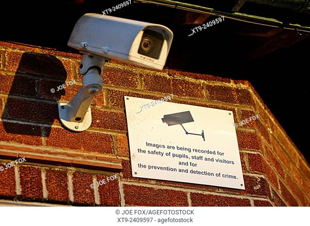 cctv camera and warning notice on a school wall