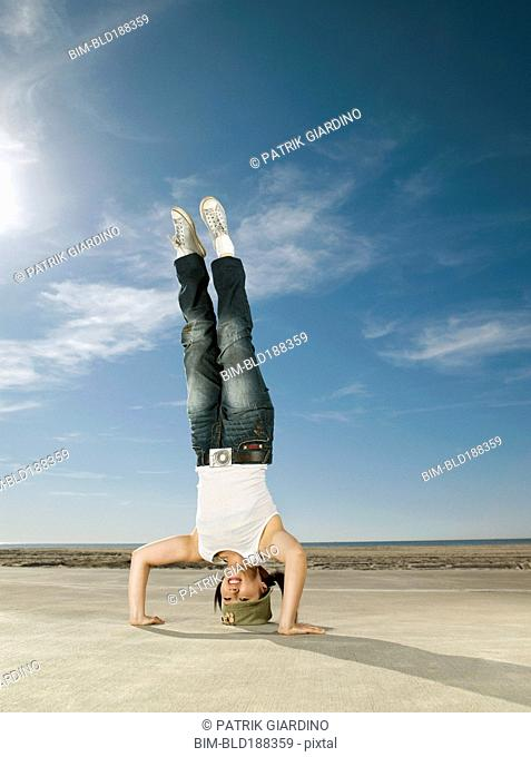 Asian woman doing headstand