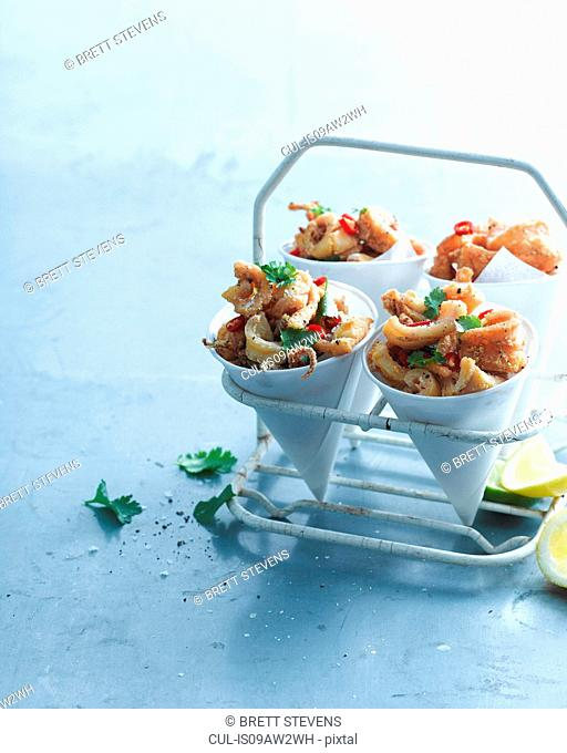 Salt and pepper chilli squid garnished with lemon and coriander in paper cones