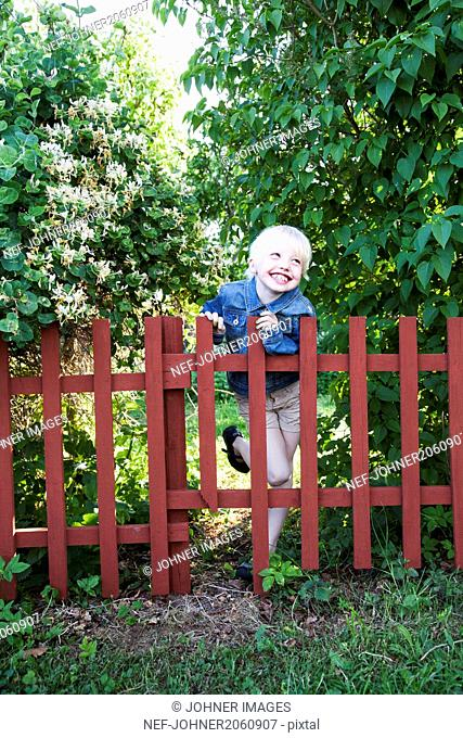 Girl standing by fence