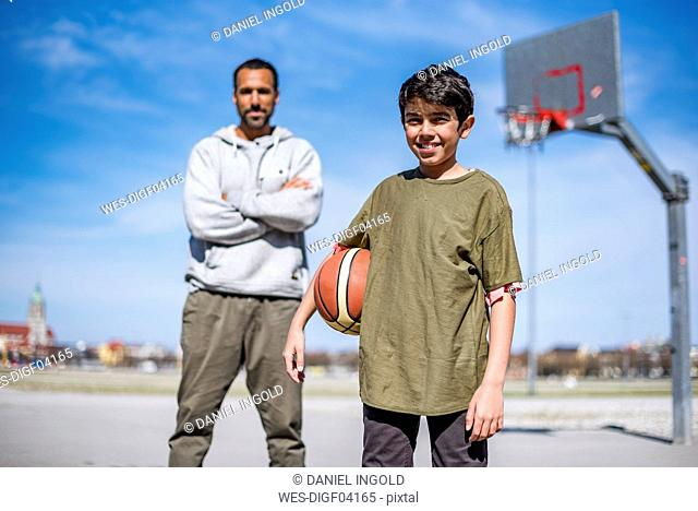 Portrait of boy with father on basketball court outdoors