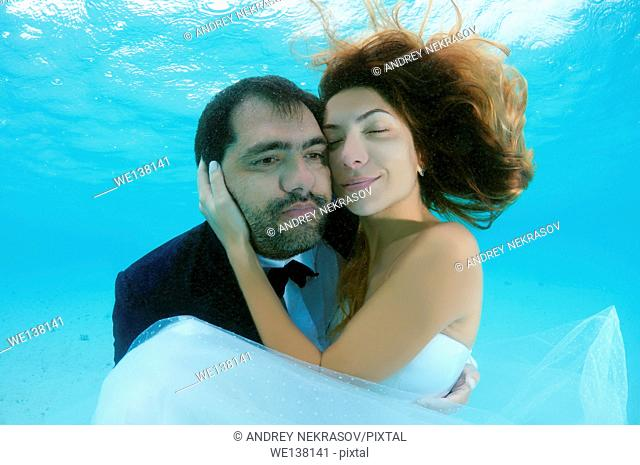 The groom holds his bride in his arms under the water, Indian Ocean, Maldives
