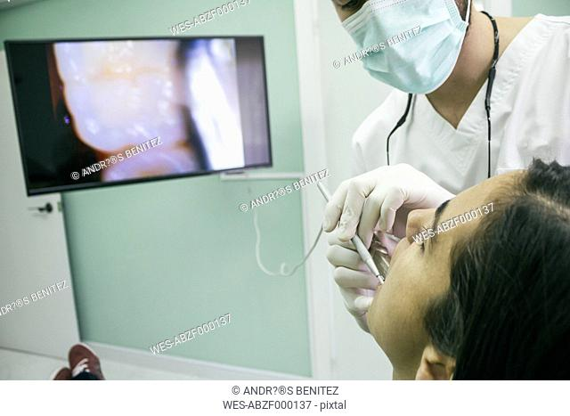 Dentist examining the mouth of a patient with an intraoral camera