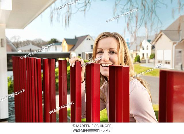Smiling woman standing behind red fence of residential house