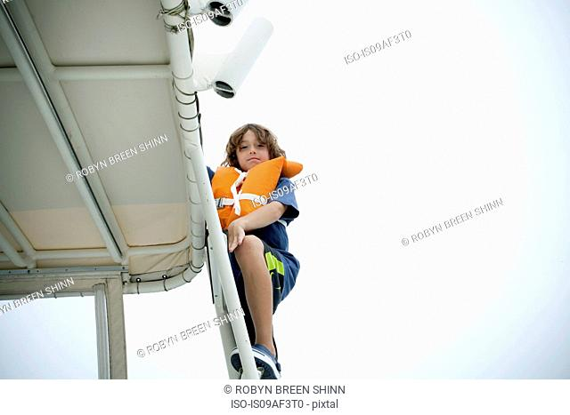 Young boy in life jacket climbing up boat steps