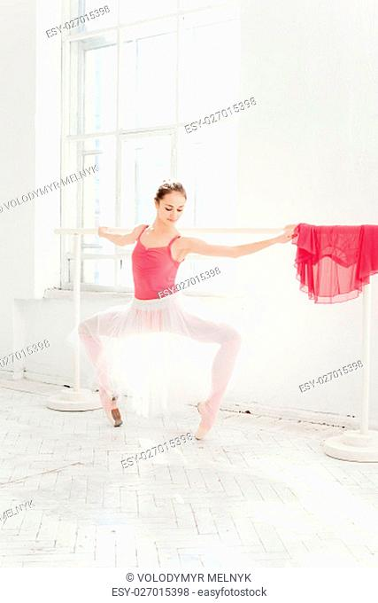 Ballerina in white and red dress posing in pointe shoes at white wooden pavilion