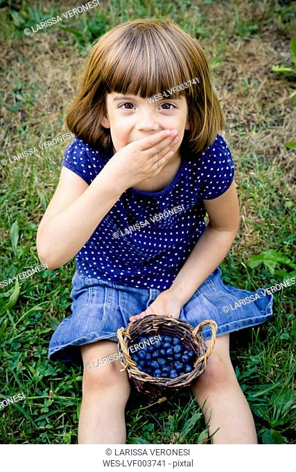 Little girl eating blueberries
