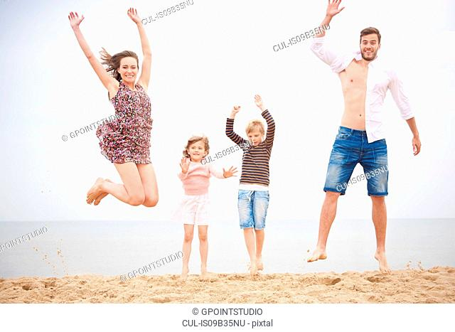 Family jumping on beach