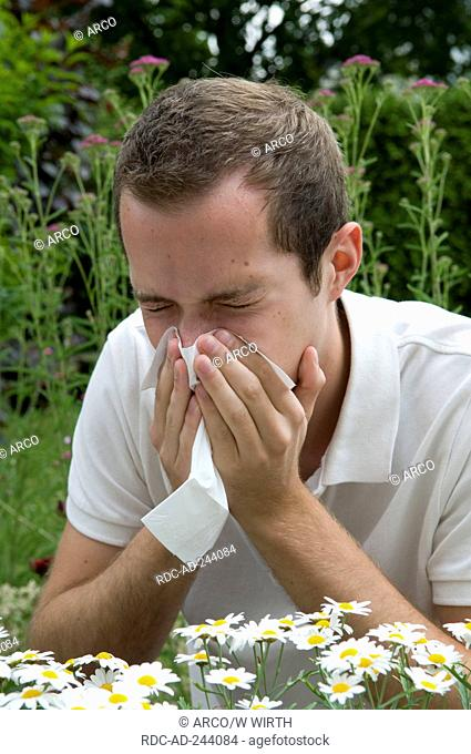 Young man with hay fever sneezing pollen allergy