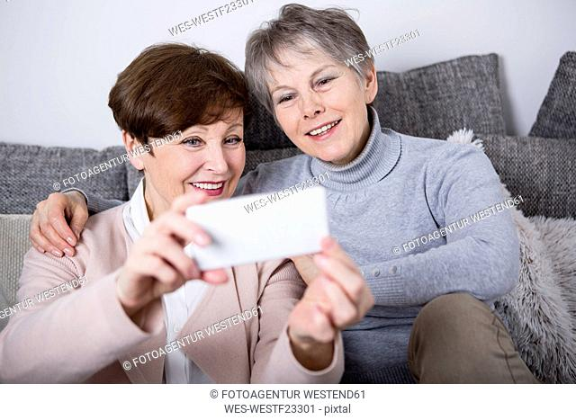 Two senior women sitting on couch, taking selfies