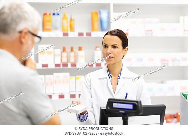 apothecary showing drug to senior man at pharmacy