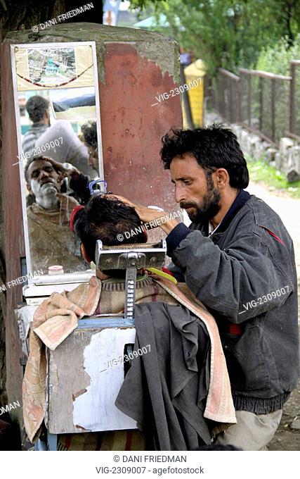 INDIA, PAHALGAM, 28.06.2010, A Kashmiri roadside barber gives a customer a shave under a tree. - PAHALGAM, KASHMIR, INDIA, 28/06/2010