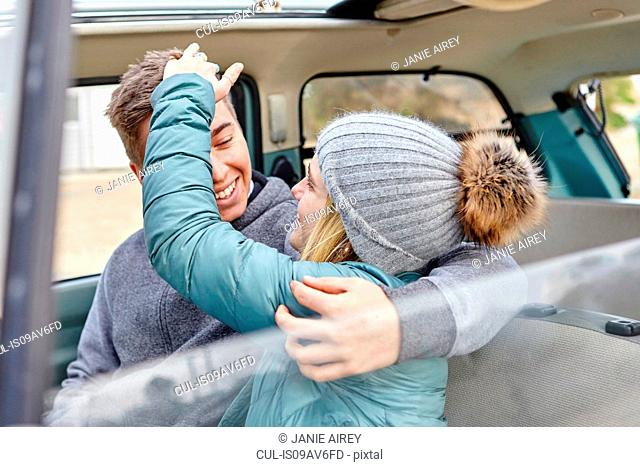 Young couple in front seat of car at beach
