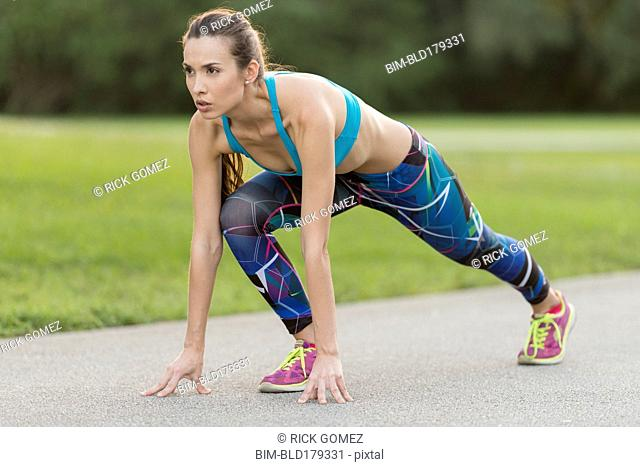Mixed race woman stretching on road