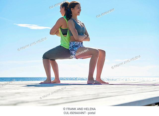 Women crouching on pier back to back arms crossed