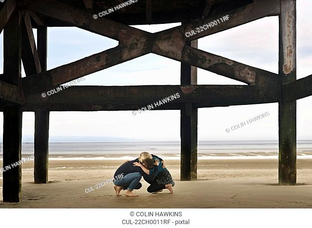 Couple sheltering on beach
