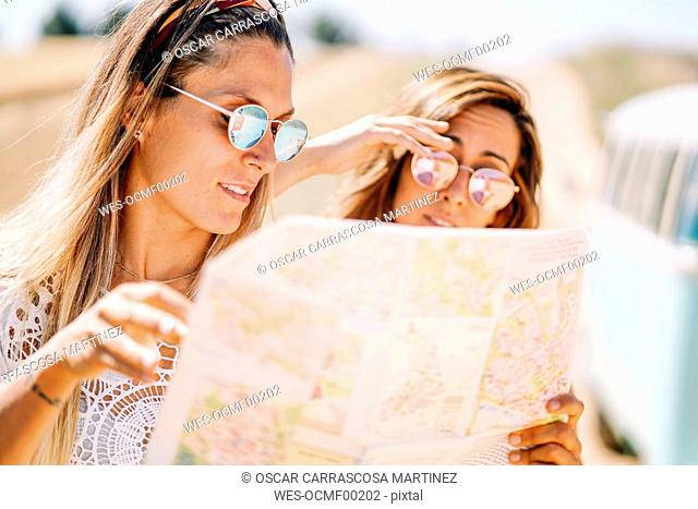 Two young women on roadtip orientating with map