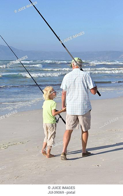Grandfather and grandson with fishing rods on sunny beach