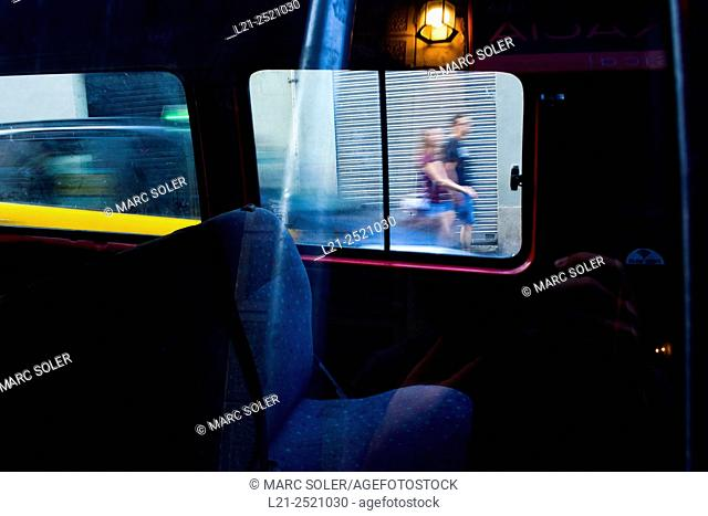 Urban scene through the windows of a car. Blurred man and woman walking down the street. Taxi moving, blur. Barcelona, Catalonia, Spain
