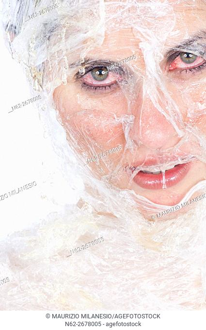Face of a girl wrapped in plastic wrap, she is doing a beauty treatment with honey, her eyes are red with irritation