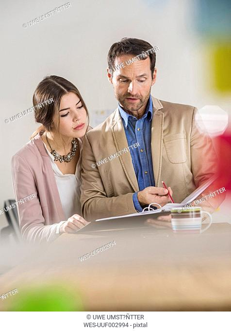 Businessman and busineswoman with file folder talking in office
