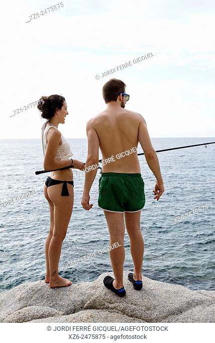 Young couple fishing at sea in the morning, Tossa de Mar, Catalonia, Spain, Europe