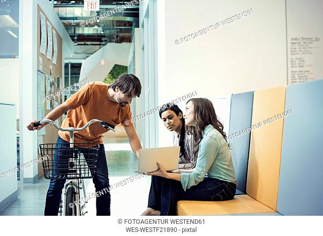 Young man on bicycle talking to colleages using laptop